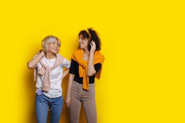 곱슬 머리를 가진 매력적인 백인 여성은 헤드폰을 통해 음악을 들으면서 빈 공간이있는 노란색 벽에 포즈를 취하고 있습니다.