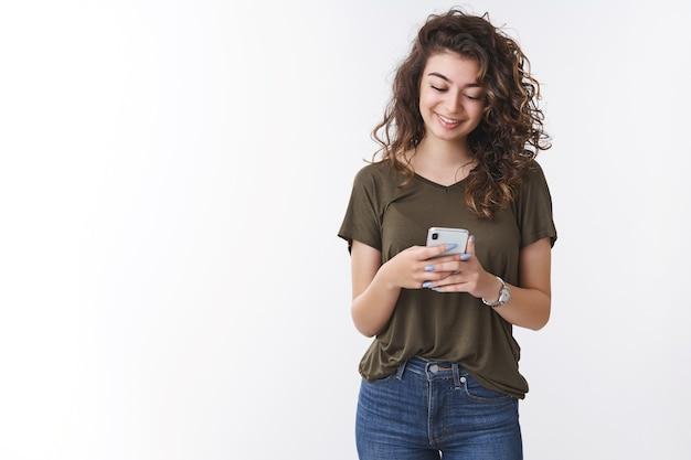 스마트폰을 들고 있는 매력적인 조지안 젊은 곱슬머리 여성은 스마트폰을 보고 웃고 있는 모습을 보고 웃고 있으며, 흰색 배경에 서 있는 소셜 네트워크를 통해 좋은 소식을 받고 기뻐합니다.