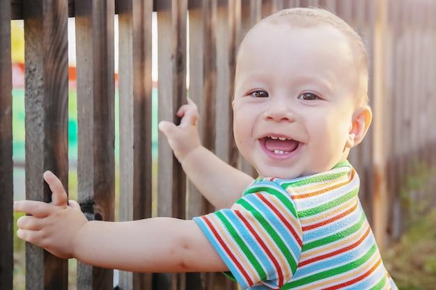 歩くか、屋外で最初の一歩を踏み出すことを学ぶ魅力的な陽気な子供、クローズアップ