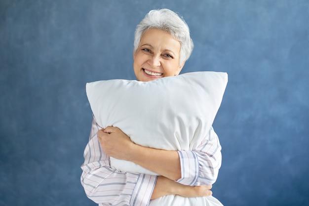 彼女は十分な睡眠をとったので幸せそうな表情をしていて、白い羽毛枕を抱き締めて、そして広く笑っている縞模様のパジャマの魅力的な陽気な成熟した女性