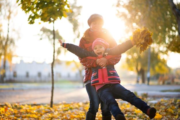 매력적인 쾌활한 어머니는 화창한 날 공원에서 산책하는 동안 노란색 단풍잎 꽃다발을 손에 들고 재미있는 딸을 안아줍니다. 변화하는 계절의 기쁨의 개념