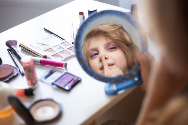 Charming child, little beauty, cute girl of 7-8 years old with beautiful blond curls, make-up, mom's makeup at the table