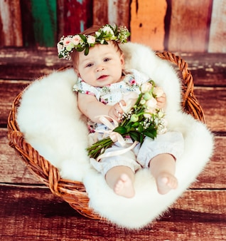 Charming child in rose wreath lies on fluffy blanket in brown basket
