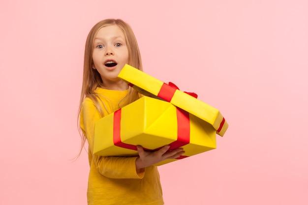 생일 선물에 놀란 매력적인 아이. 선물 상자를 열고 놀란 표정으로 입을 벌리고 있는 귀여운 소녀의 초상화. 분홍색 배경에 고립 된 실내 스튜디오 촬영
