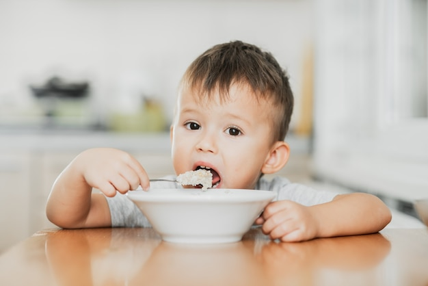 A charming child in a tshirt in the kitchen eats oatmeal very greedily