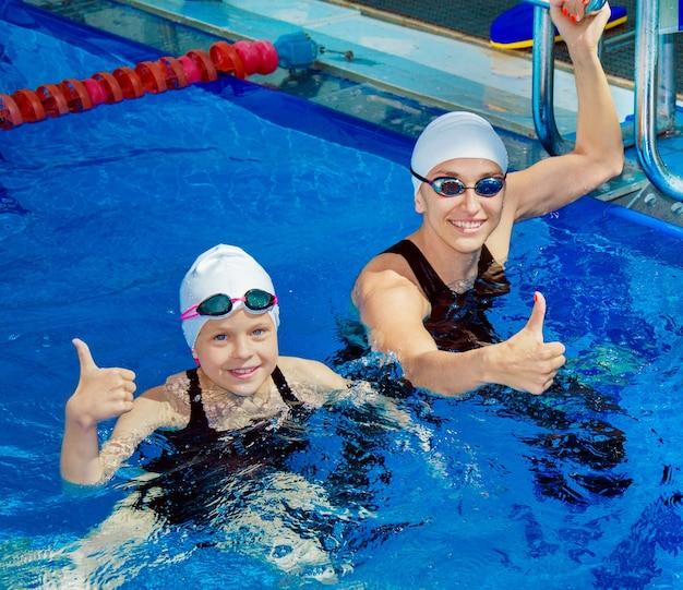 Очаровательный тренер со своим учеником плавает в бассейне и улыбается