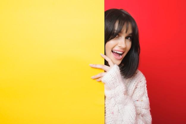 赤の明るい空の黄色い紙の後ろから見ている魅力的なコンテンツの女性