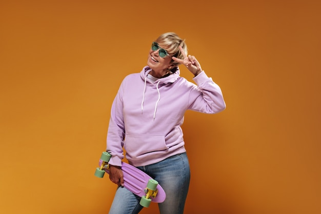 Charming cool woman with blonde modern hairstyle in green glasses and pink oversize hoodie smiling, showing peace sign and posing with skateboard on orange background.