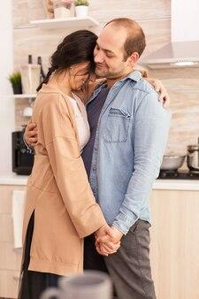 부엌에서 춤추는 매력적인 커플. 행복한 젊은 가족. 아내와 남편의 사랑, 로맨스, 부드러운 순간, 집에서의 재미와 행복, 공생 음악 쾌활하고 미소