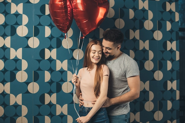 Charming couple embracing on a blue  wall holding balloons and dating on valentines day