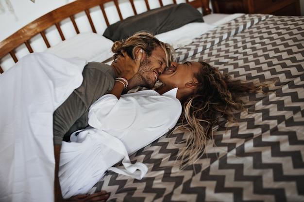 楽しんで、ベッドに横になって、抱き締める魅力的なカップル。