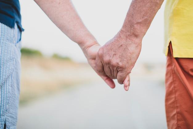 永遠の愛の約束として手を繋いでいる魅力的なカップル