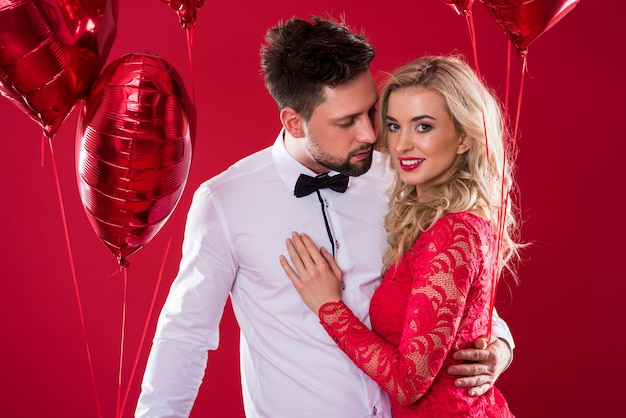 赤い光沢のある風船の2つの束を保持している魅力的なカップル