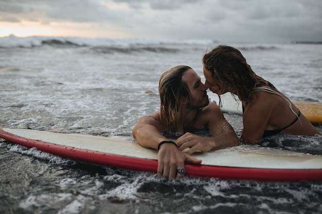 Charming couple kissing during sunset on surfboard