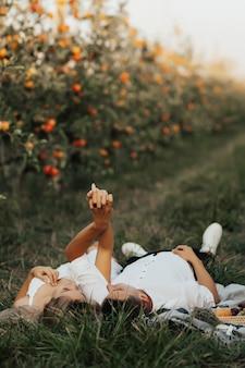 녹색 잔디에 담요에 누워 매력적인 커플입니다. 여름 피크닉에 시간을 보내는 편안한 커플.