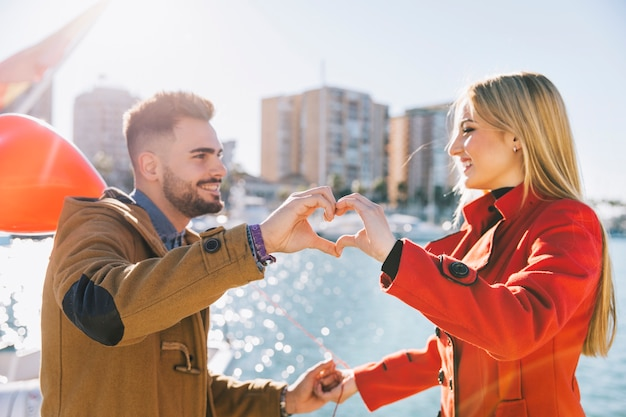Charming couple showing heart with hands