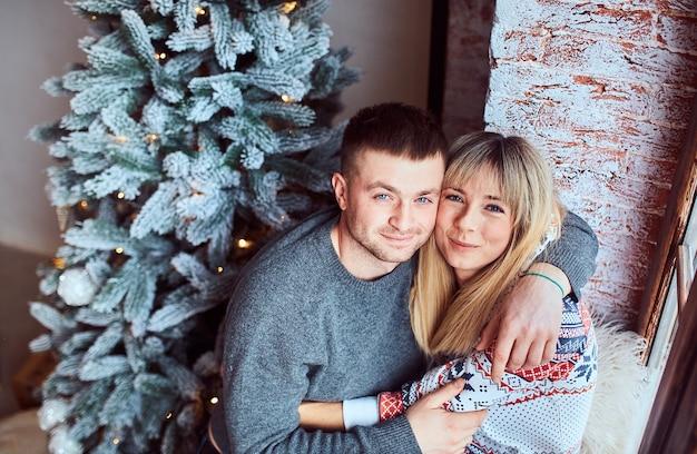 매력적인 부부는 창과 크리스마스 트리 근처에 앉아
