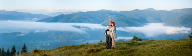 Charming couple toourists standing together on a hill, enjoying morning haze over the mountains and forests. panorama