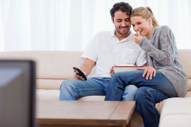 Charming couple watching tv while eating popcorn