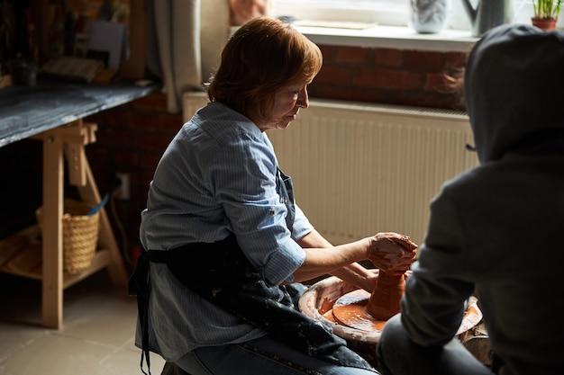 Очаровательная мастерица в фартуке месит и лепит глину на гончарном круге, пока подруга наблюдает за процессом