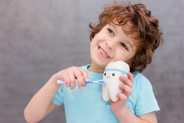 Очаровательный кудрявый мальчик без зубов улыбается на серой стене. мальчик потерял первый молочный зуб. концепция здоровых зубов, стоматологическая клиника.
