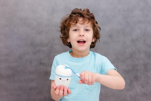 Очаровательный кудрявый мальчик улыбается без зуба на белой поверхности. мальчик потерял первый молочный зуб. концепция здоровых зубов. стоматологическая клиника.