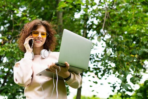 도시 녹색 공원에 노트북 전화와 매력적인 곱슬 소녀. 프리랜서 개념
