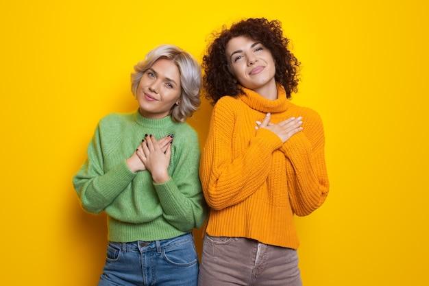 노란색 벽에 사랑을 몸짓으로 손바닥으로 마음을 만지는 매력적인 곱슬 머리 자매