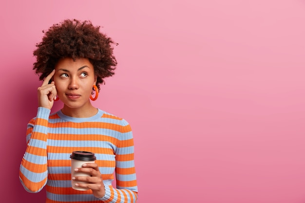 Affascinante donna dai capelli ricci tiene il dito sulla tempia, ha un'espressione premurosa, vestita con un maglione a righe casual, beve caffè da asporto, si alza