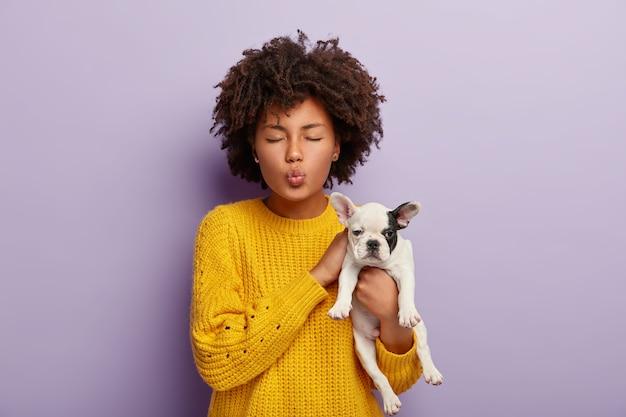 매력적인 곱슬 머리 여자가 사랑스러운 애완 동물 돌봐