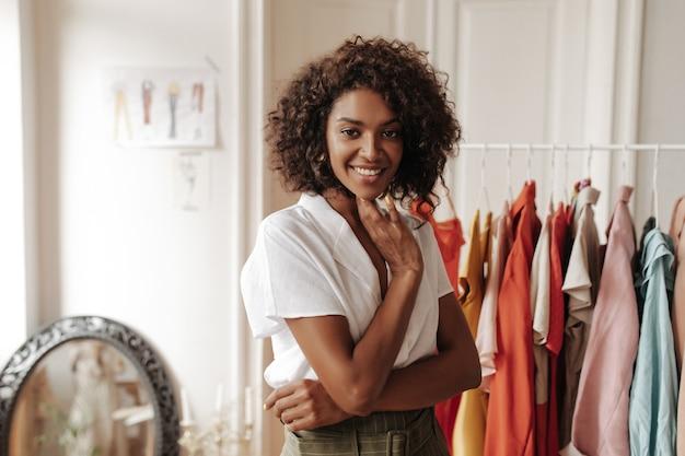 흰 블라우스를 입은 매력적인 곱슬머리 여성은 진심으로 웃고, 정면을 바라보며 아늑한 탈의실에서 포즈를 취합니다.