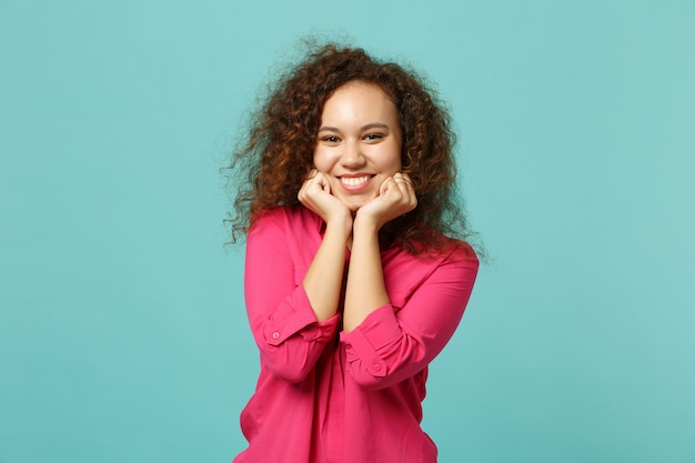 Charming cute african girl in casual clothes looking camera, put hand prop up on chin isolated on blue turquoise background in studio. people sincere emotions, lifestyle concept. mock up copy space.