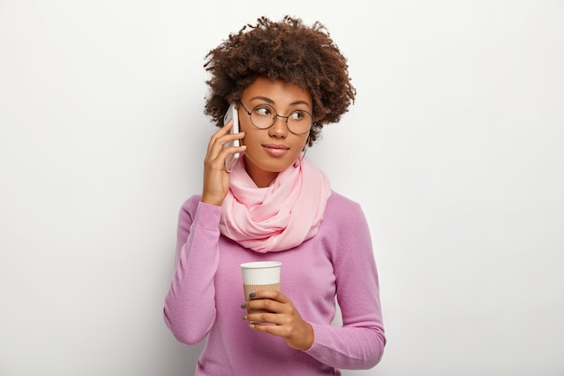 Charming cute calm woman with dark skin, curly hairstyle, looks aside, makes call via smart phone, holds disposable cup of tea, wears purple turtleneck with scrarf