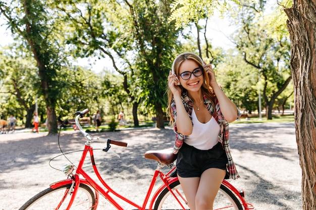 公園で音楽を聴いている夏の服装の魅力的なかわいい女の子。自転車の横に立っているヘッドフォンで陽気な金髪モデルの屋外写真。