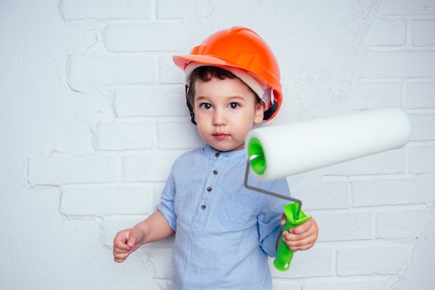 헬멧 안전모를 쓴 매력적인 귀여운 소년은 흰색 페인트로 벽을 칠했습니다. 수리 집 아파트의 개념입니다.