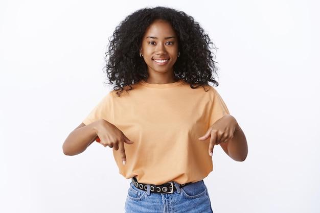 매력적인 젊은 아프리카계 미국인 20대 여성 아프리카 헤어컷은 재미있는 제안, 판촉 활동, 서 있는 흰 벽을 보여주는 친근한 검지 손가락을 아래로 가리키며 웃고 있습니다.