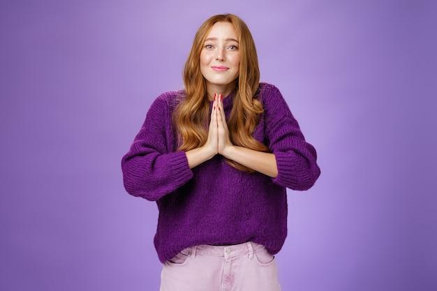 Affascinante donna rossa carina con capelli lunghi e lentiggini in maglione viola che si tiene per mano in preghiera facendo sorridere speranzoso e l'angelo sembra implorare aiuto o pietà, chiedendo con supplica.