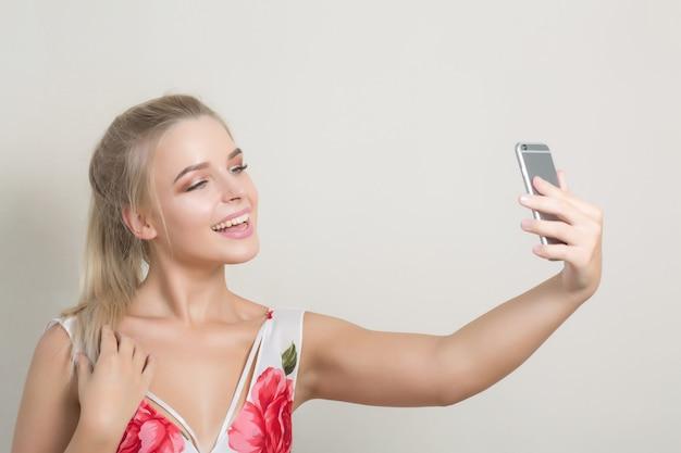 灰色の背景に対してスマートフォンで自画像を作る魅力的なかわいい女性