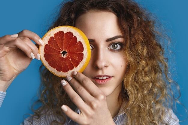 緑の目とボリュームのある髪のポーズで、ジューシーな熟したグレープフルーツのラウンドの後ろに片目を隠して、魅力的なかわいい若い女性。鮮度、ビタミン、健康、ケア、美容、ウェルネスのコンセプト