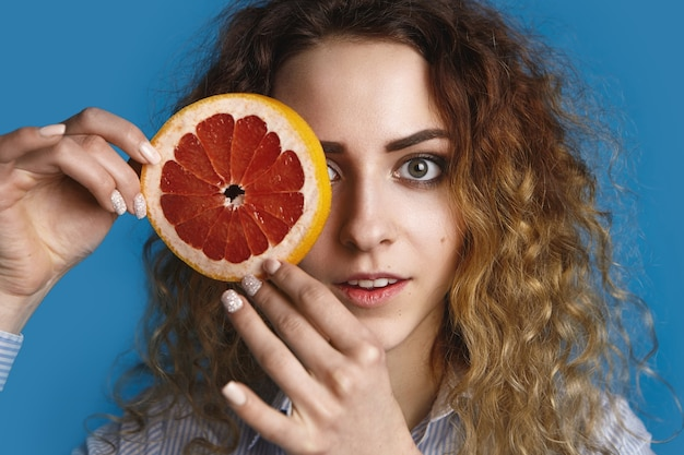 Charming cute young female with green eyes and voluminous hair posing , hiding one eye behind round of juicy ripe grapefruit. freshness, vitamins, health, care, beauty and wellness concept