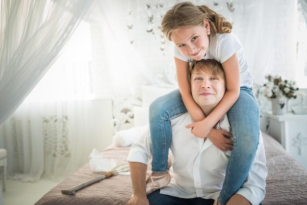 매력적인 아빠와 십대 딸이 아름다운 세련된 방에서 소파에 앉아 있습니다.