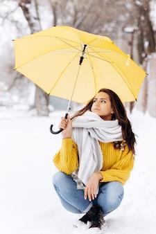 Очаровательная темноволосая девушка, одетая в желтый свитер, джинсы и белый шарф, сидит на дороге под желтым зонтом в снежный зимний день.