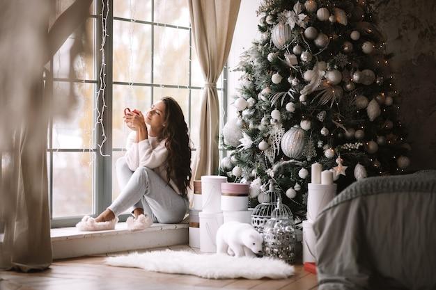 바지, 스웨터, 따뜻한 슬리퍼를 입은 매력적인 검은 머리 소녀는 새해 나무, 선물, 양초 옆에 있는 탁 트인 창문의 창턱에 빨간 컵을 들고 있습니다.