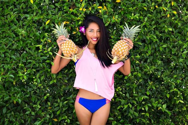 パイナップルを押しながら笑顔で見下ろしている魅力的な黒髪の女の子。ブッシュの背景にポーズをとって長い髪の紫色の花と青いビキニで日焼けしたアジアの女性の屋外のポートレート。