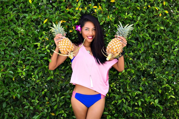 Charming dark-haired girl holding pineapples and looking down with smile. outdoor portrait of tanned asian lady in blue bikini with purple flower in long hair posing on bush background.