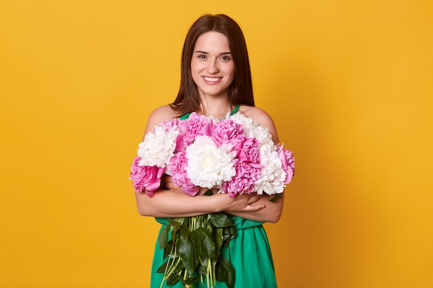 Charming dark haired woman posing in green dress, embracing bouquet of flowers