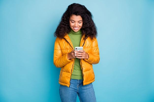 フォロワーをチェックする電話の手を握っている魅力的な暗い肌の女性加入者は黄色の春のオーバーコートジーンズセーター孤立した青い色の壁を着ています