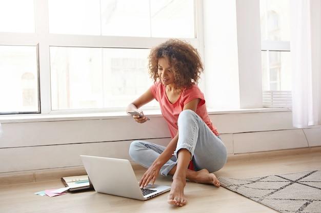 Очаровательная темнокожая кудрявая женщина сидит у большого окна, держит в руке смартфон и проверяет почту на ноутбуке, носит повседневную одежду
