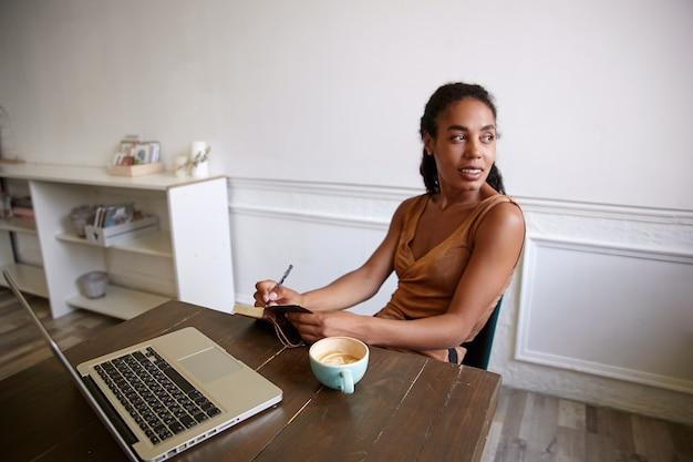 Очаровательная темнокожая кудрявая женщина работает за деревянным столом с современным ноутбуком, пишет заметки в ежедневнике, смотрит в сторону с легкой улыбкой