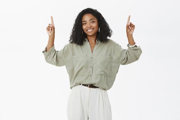 Очаровательная темнокожая модель с кудрявой прической в модной блузке и штанах поднимает руки и указывает вверх